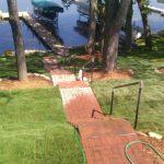 brick walkway that leads down to a lake shore